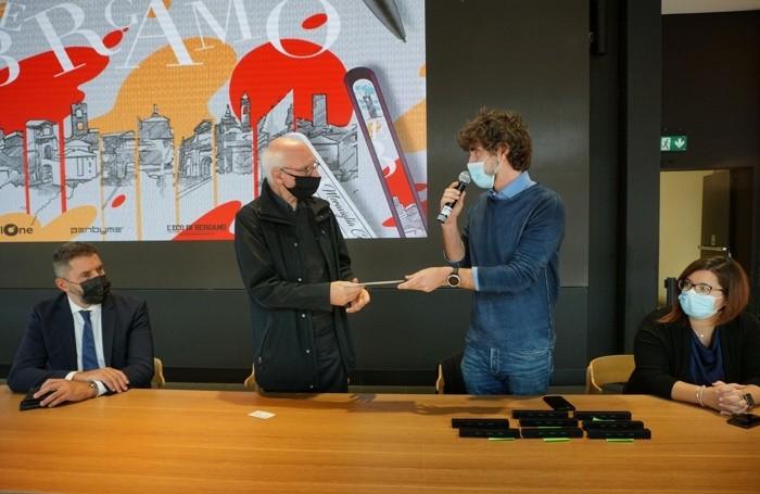 Luca Carminati consegne il ricavato dell'asta del progetto «PenbymeXBergamo» a don Davide Rota. Ai lati Ruggero Pizzagalli e Antonia Larino, rispettivamente direttore e responsabile marketing di Oriocenter